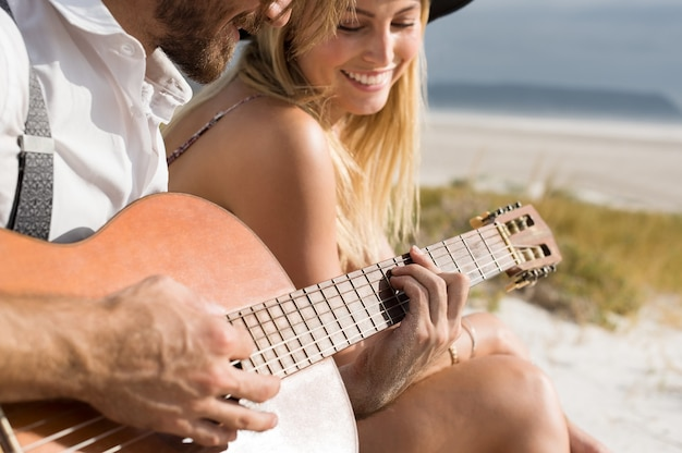 Close up of young man playing an acoustic guitar on the beach