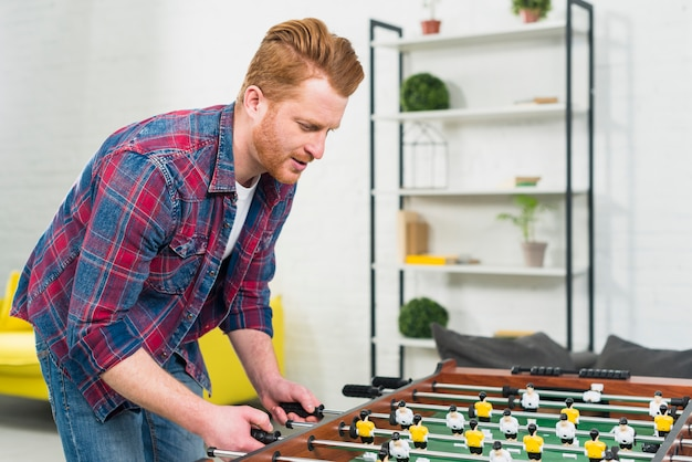 Close-up of young man playing the football table soccer game at home