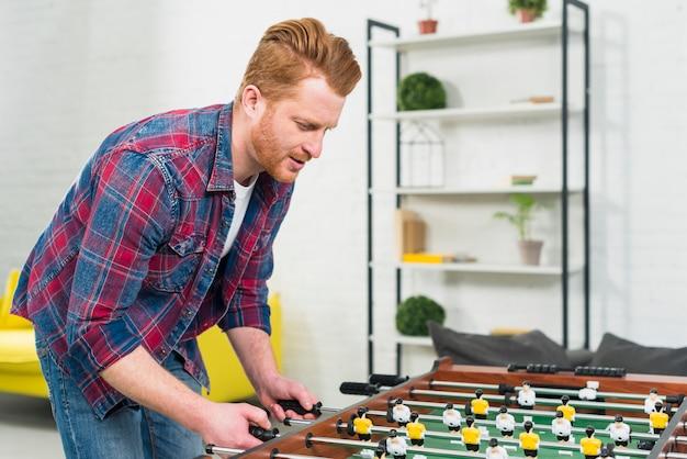 Primo piano del giovane che gioca il gioco di calcio della tavola di calcio a casa
