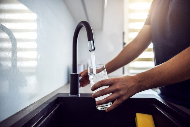 Close up of young man pouring fresh water from kitchen sink. home interior.