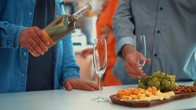 Close up of young man pouring white wine in glasses. two generations tasting a cup of champagne in cozy dining room while women preparing the healthy dinner