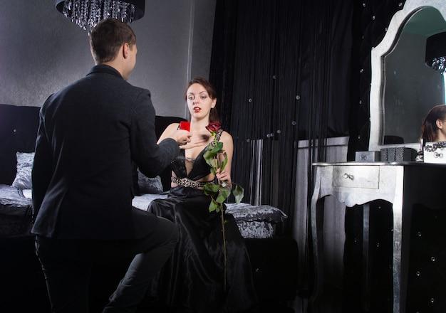 寝室で彼のガールフレンドにプロポーズしている若い男をクローズアップ。