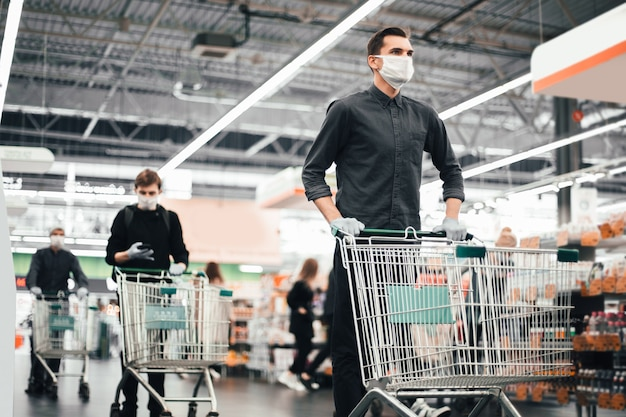 Close up. young man in a protective mask with a shopping cart
