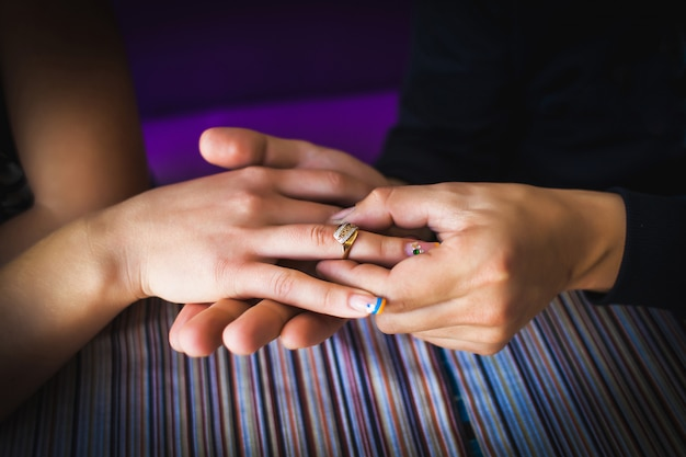 Close up of young man putting on girlfriend finger engagement ring during romantic dinner.
