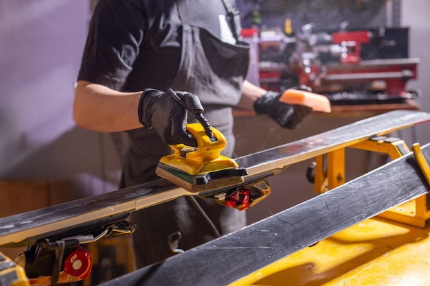 Close up of young man repairing the ski in the service