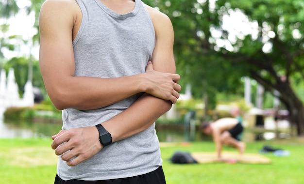 若い男のランナーを閉じる肘と腕の筋肉に怪我や痛みがある