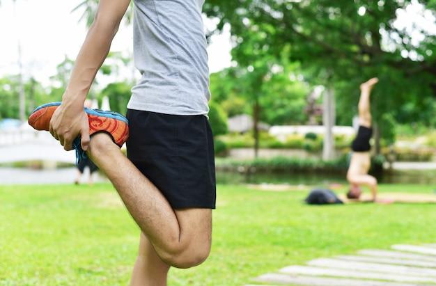 日没時にトレーニングする前に、若い男性ランナーのウォームアップとストレッチをクローズアップ