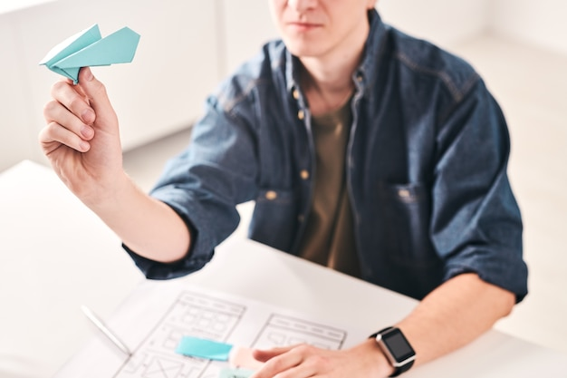 Close-up of young man sitting at table and throwing paper plane while working on ui design in office