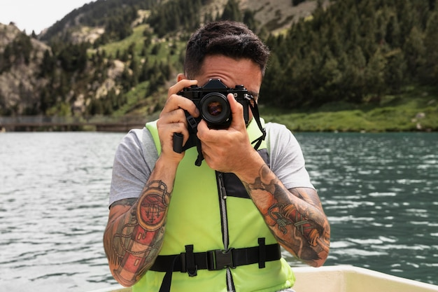 Close up on young man taking pictures with camera