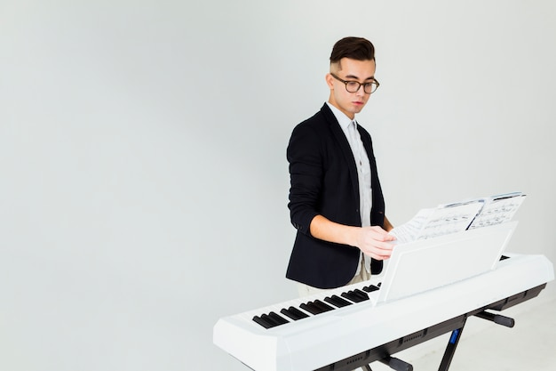 Close-up of a young man turning the pages of musical sheet on piano isolated on white background