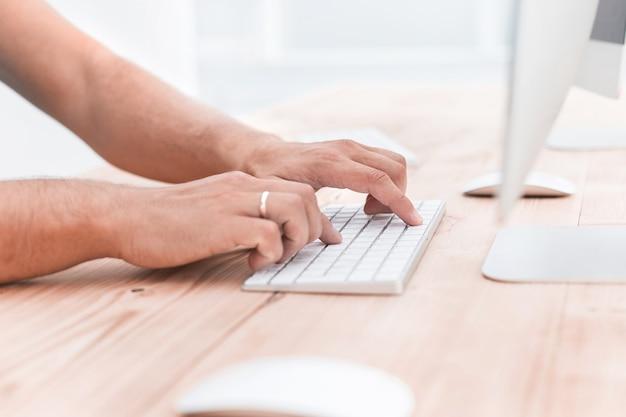 Закройте вверх. молодой человек печатает на клавиатуре компьютера