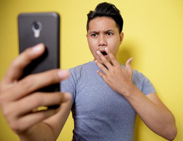 Крупным планом молодой человек, очень удивленный, глядя на телефон, изолированный на стене желтого цвета
