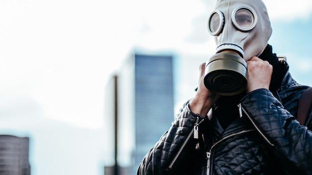 확대. 도시 거리에 가스 마스크를 쓰고 젊은 남자