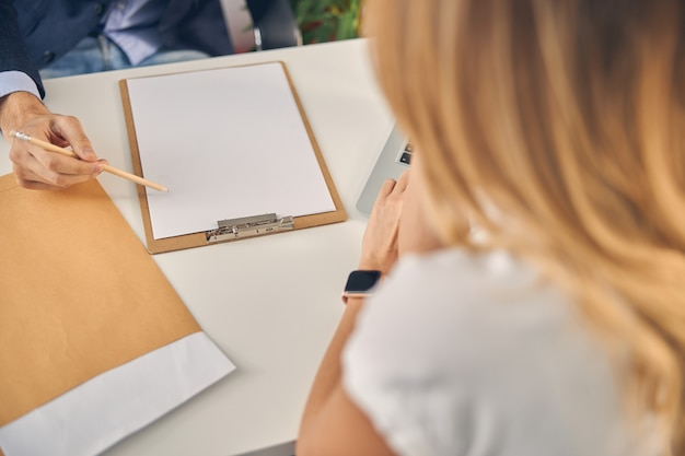 Close up of young man working with female coworker while sitting at the table with clipboard and blank sheet of paper