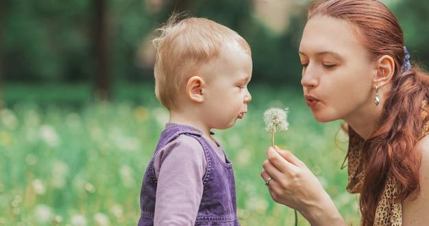 Крупным планом. молодая мама с маленькой дочкой дует на одуванчик