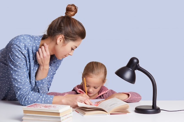 若い母親を閉じると、娘が作文を書くのに役立ち、読書灯を使用し、女の子は白で隔離され、集中して見えます。子供と学習の概念。