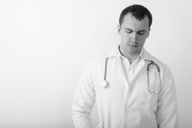 Close up of young muscular man doctor thinking while looking down
