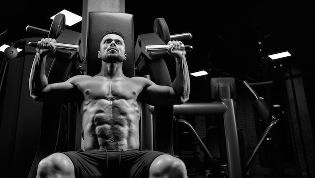 Close up of young muscular man sitting on simulator in gym.