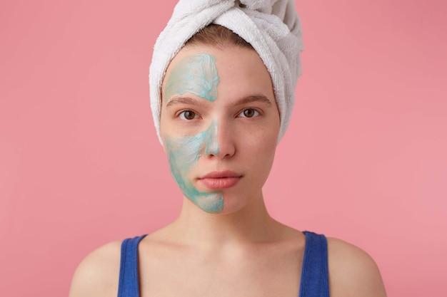 Primo piano di giovane bella signora con un asciugamano sulla testa dopo la doccia, mettere una maschera sul pavimento per confrontare l'effetto, sembra si leva in piedi