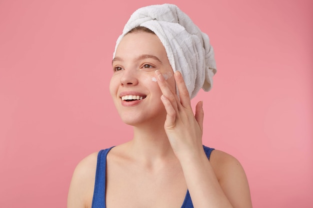 Close up of young nice woman with natural beauty with a towel on her head after shower, smiling, looking away and puts on face cream.