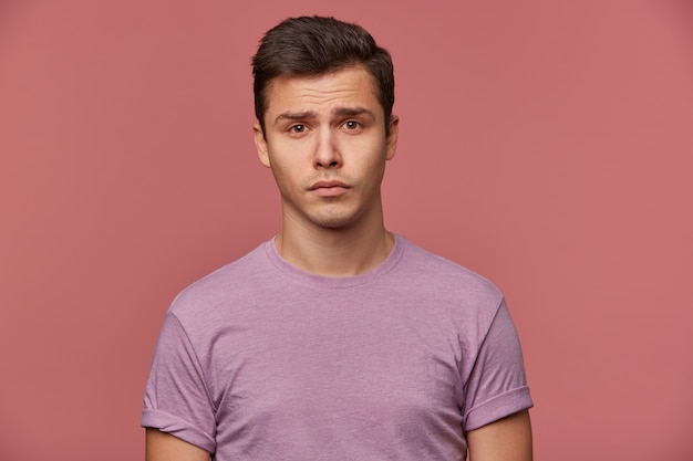 Close up of young offended attractive boy in blank t-shirt, stands over pink background and looks sad and unhappy.