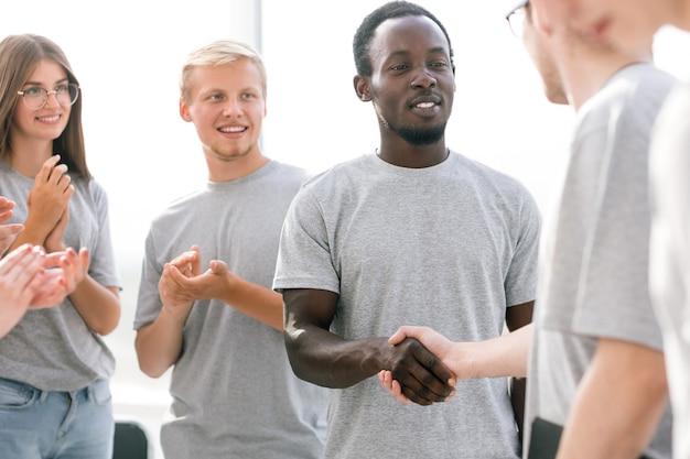 閉じる。握手するビジネスセミナーの若い参加者