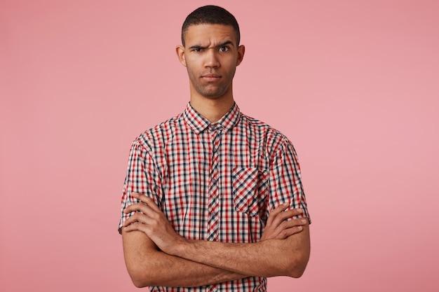 Primo piano di giovane ragazzo dalla pelle scura dispiaciuto in camicia a scacchi, malcontento guarda la telecamera, si erge su sfondo rosa con le braccia incrociate e le sopracciglia alzate.