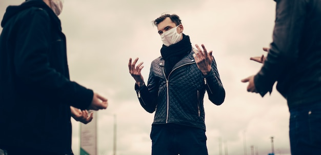 閉じる。保護マスクをした若者が街の通りでコミュニケーションをとる