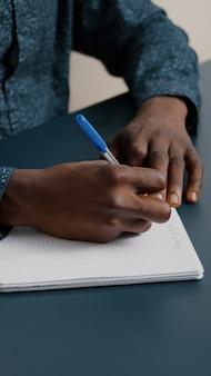 Primo piano di un giovane che prende appunti sul blocco note usando una penna