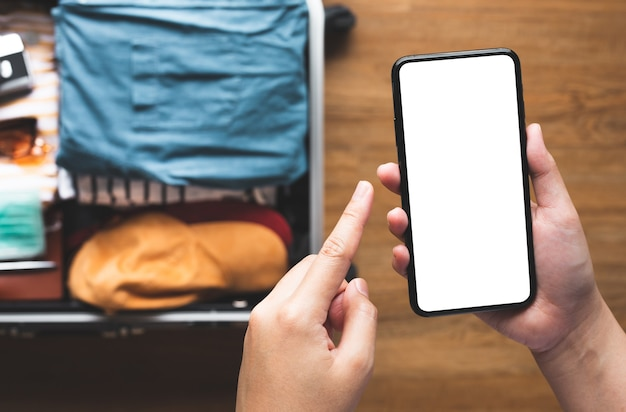 Close up young person using smartphone with blank screen on suitcase.