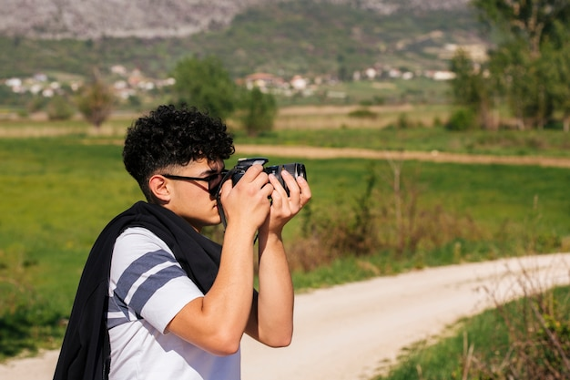 Close-up of young photographer taking nature photograph
