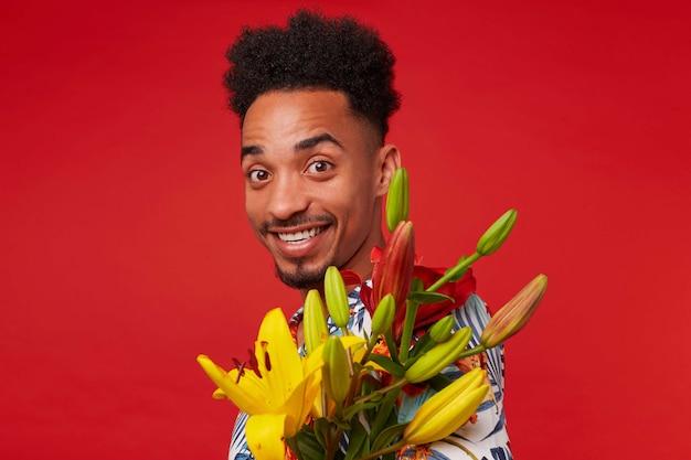 若いポジティブな暗い肌の男をクローズアップ、アロハシャツを着て、幸せな表情でカメラを見て、黄色と赤の花を保持し、赤い背景の上に立って笑顔。