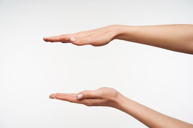 Chiuda in sulle mani della giovane signora graziosa con il manicure bianco che misura gli oggetti invisibili
