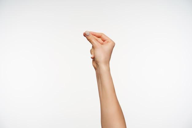 Primo piano sulla mano alzata della giovane donna graziosa che tiene insieme il pollice e il dito medio