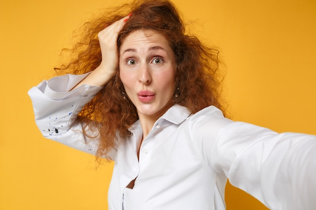 Close up of young redhead woman girl in white shirt posing isolated on yellow orange wall