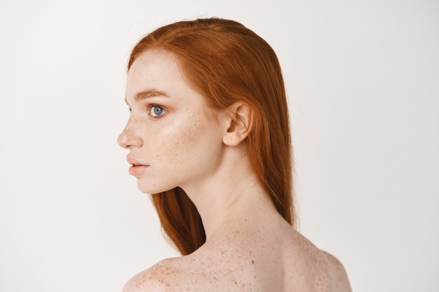 Close-up of young redhead woman looking left, turn head at promo banner, standing naked on white wall