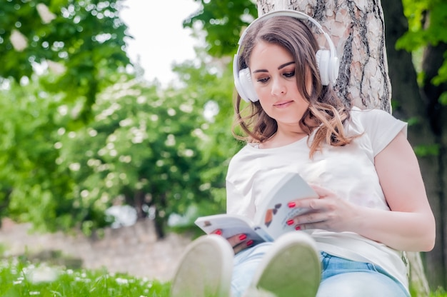 Close-up of young relaxed woman reading and listening music on headphones outside in a spring day. freetime concept with beautiful female relaxing outdoors with music, books and coffee