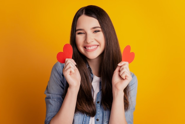 Close-up of young romantic affectionate woman hold two little hearts on yellow background