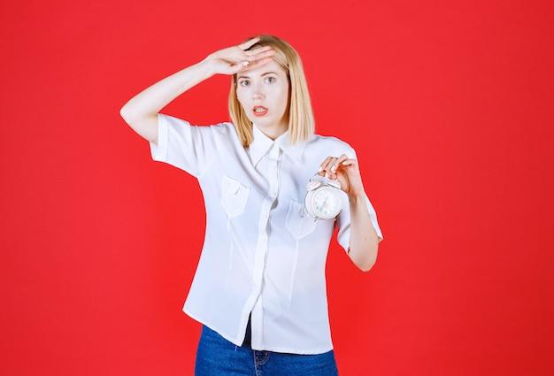 赤い壁に分離された時計を保持している若い怖い女性をクローズアップ