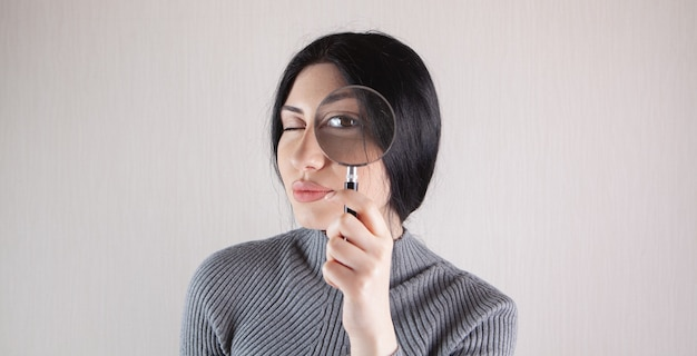 Close up of young serious brunette woman looking through magnifying glass