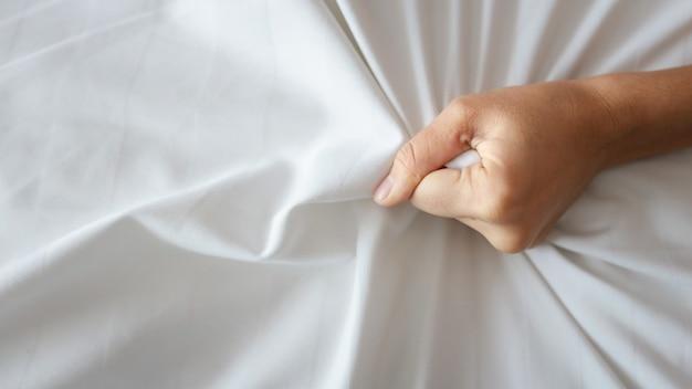 호텔에서 엑스터시에 흰색 시트를 당기는 젊은 섹시한 여자 손을 닫습니다