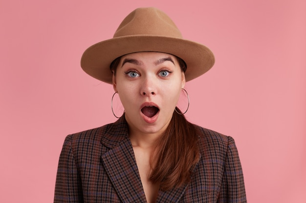 Close up of young shocked attractive lady, wearing in checkered jacket and brown hat. looking at the camera with wide open mouth and ayes.