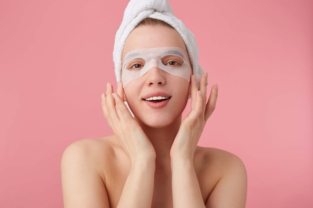 Close up of young smiling happy woman after spa with a towel on her head, with mask for eyes, broadly smiles, looks positive, stands.