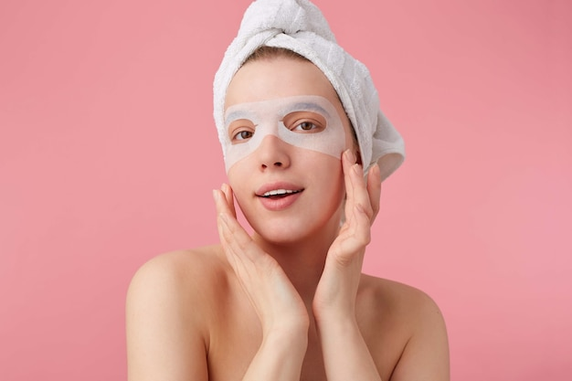 Close up of young smiling happy woman after spa with a towel on her head, with mask for eyes, broadly smiles, looks positive, touches her cheeks, stands.