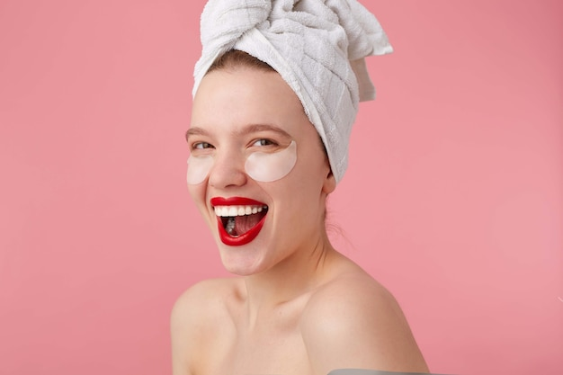 Close up of young smiling lady after shower with a towel on her head, with patches and red lips, looks happy, stands.