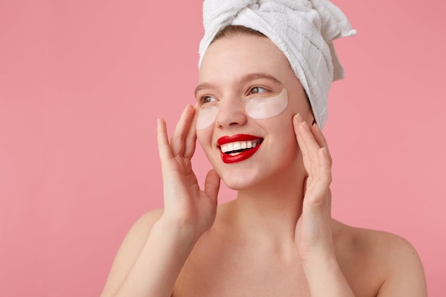 Close up of young smiling lady after shower with a towel on her head, with patches and red lips, touches face and looks happy, stands.