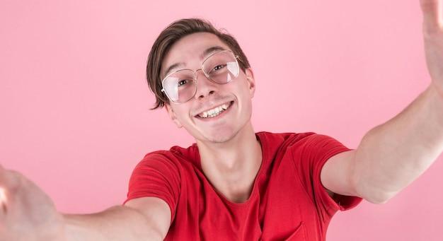 ピンクの壁の背景、スタジオの肖像画に分離されたポーズでカジュアルな服を着た若い笑顔の男性をクローズアップ。人々の誠実な感情のライフスタイルの概念。コピー用のコピースペース。