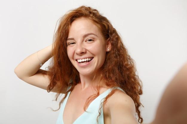 Chiuda in su giovane ragazza sorridente della donna della testarossa in vestiti leggeri casuali che posano isolati su fondo bianco, ritratto dello studio. concetto di stile di vita della gente. mock up copia spazio. facendo selfie sul telefono cellulare.