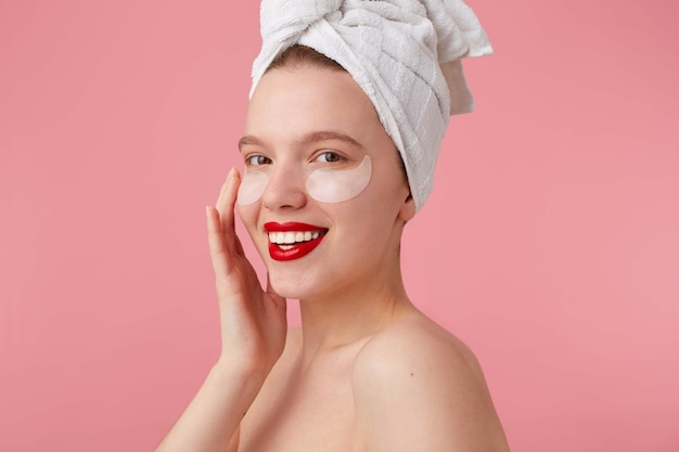 Close up of young smiling woman with a towel on her head after shower, with patches and red lips, touches face and looks happy, stands.