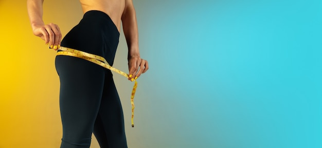Close up of young and sportive woman with fit belly and measurer on gradient background perfect body